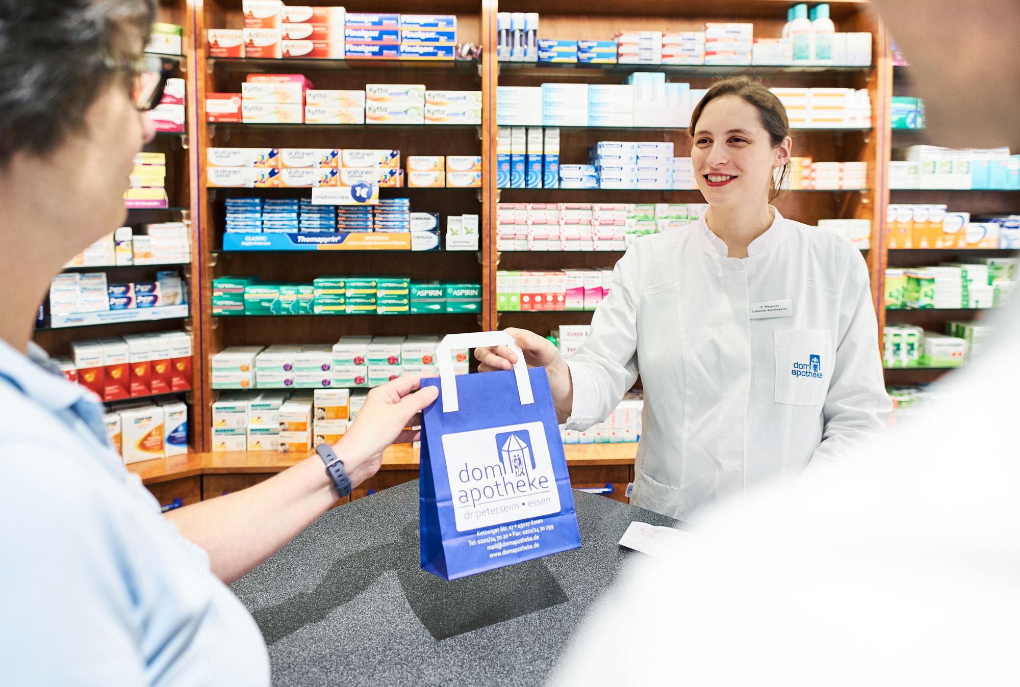 Mitarbeiterin überreicht Kundin Medikamente in der Dom-Apotheke